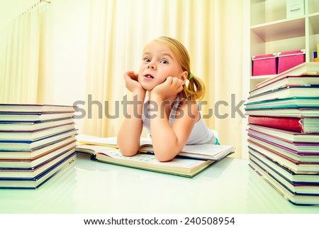 Five year old girl sitting at table at home with piles of books and dreams. Educational concept.