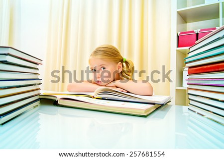 Five year old girl sitting at table at home with piles of books and dreams. Educational concept. - stock photo