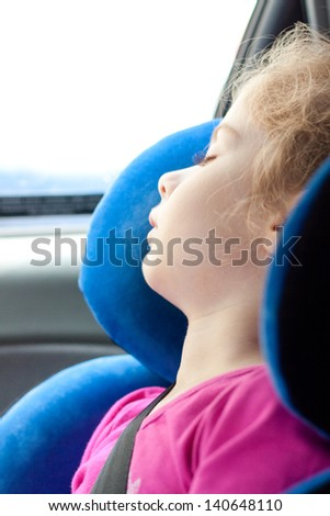 Five years old blond caucasian child girl sleeping while traveling in a car seat - stock photo