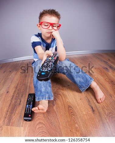 Five years old bored boy watching tv - stock photo