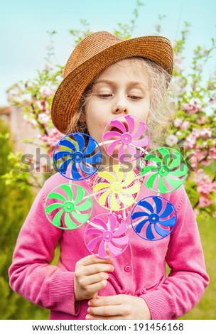 Five years old caucasian blond child girl in a hat playing windmill on blooming garden background. Spring - careless childhood. - stock photo