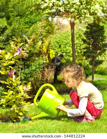 Five years old caucasian child girl water magnolia flowers in the garden during sunny spring day - stock photo