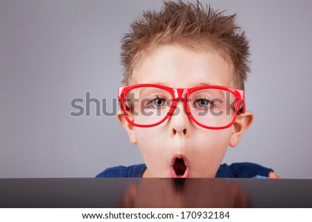 Five years old cute little boy with surprised face hiding behind a table - stock photo