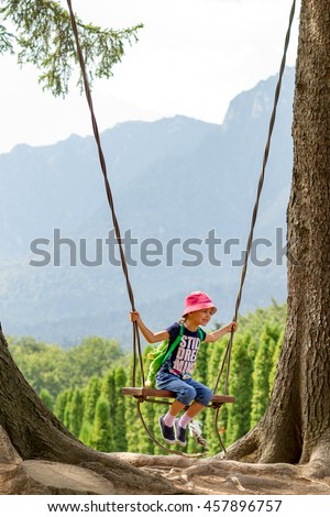 Five years old girl playing on a swing between two giant fir trees with mountains behind.