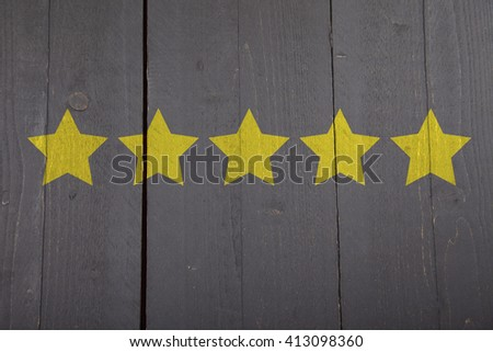 Five yellow ranking stars on black wooden background - stock photo