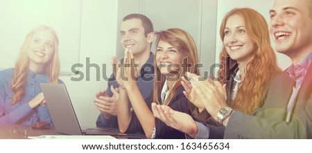 Five young business people applauding. The focus is on the girl on the right side. Lens flare and light effect - stock photo