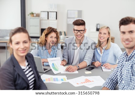 Five Young Businesspeople Smiling at the Camera While Having a Business Meeting Inside the Boardroom. - stock photo
