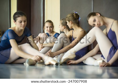 Five young dancers in the same dance costumes, resting sitting on the floor. Dance Class. Ballet School. Discussions yet with each other. - stock photo
