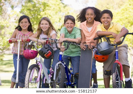 Five young friends with bicycles scooters and skateboard outdoors smiling