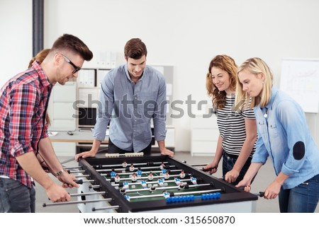 Five Young Office People Enjoying Table Soccer Game During their Free Time at the Workplace. - stock photo