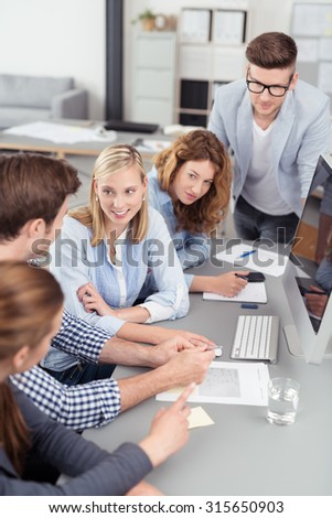 Five Young Office Workers Brainstorming for New Ideas at the Table with Computer Inside the Office.