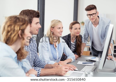 Five Young Office Workers Reading Something on Computer Together While Having a Business Meeting. - stock photo