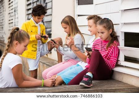 Five young smiling kidsare chatting on their smartphone on walking.