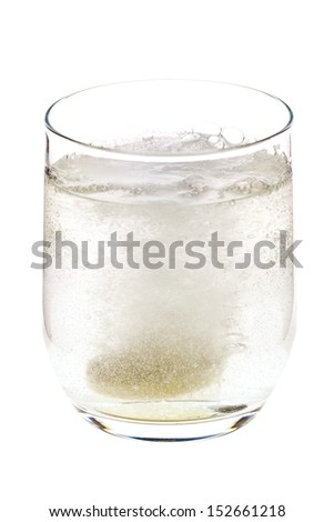 Fizzing pill tossed into the glass, dissolving and releasing bubbles, isolated on white background
