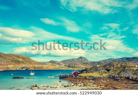 Fjord with blue water in sunny day. Barents Sea. Rocky beach, Mageroya island, Norway