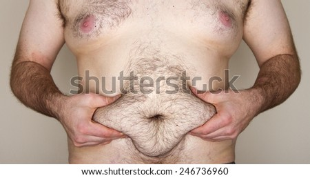 Flab, Fat, Obese, A large man grabs his mid section - stock photo