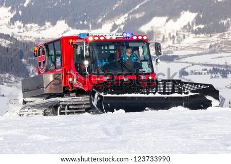 FLACHAU, AUSTRIA - DEC 29: Snow groomer on the ski piste in the ski resort town of Flachau, Austria on Dec 29, 2012. These pistes are part of the Ski Armada network, the largest of Europe. - stock photo