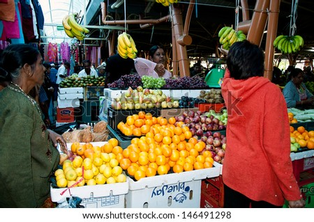 FLACQ, MAURITIUS-JUNE 23: Customers buys fruit and vegetable in the market hall on June 23, 2013 in Flacq, Mauritius
