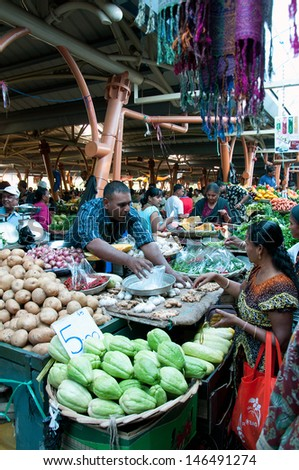 FLACQ, MAURITIUS-JUNE 23: Indian people search for a bargains in the market hall on June 23, 2013 in Flacq, Mauritius - stock photo