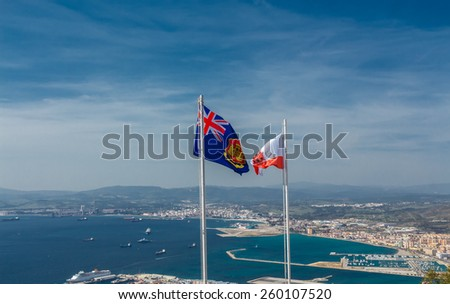 Flag and Coat of arms of Gibraltar  against the city - stock photo