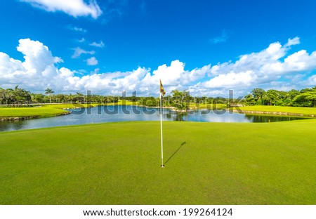 Flag and sand bunkers and a lake as a background at the beautiful golf course of the luxury Mexican resort. - stock photo