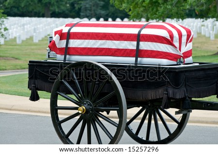 Flag draped casket on caisson being pulled to grave site in Arlington National Cemetery with grave stones in background - stock photo