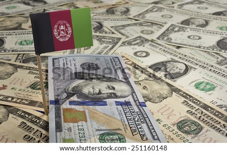 Flag of Afghanistan sticking in a variety of american banknotes.(series) - stock photo