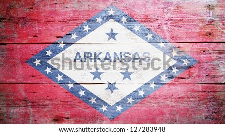 Flag of Arkansas painted on grungy wooden background - stock photo