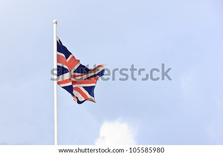 Flag of British waving on top of a pole with light blue sky. - stock photo