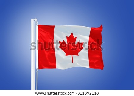 Flag of Canada flying against a blue sky. - stock photo
