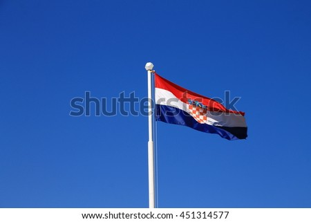 Flag of Croatia with flag pole waving in the wind with blue sky in background