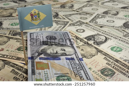 Flag of Delaware sticking in a variety of american banknotes.(series) - stock photo