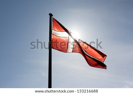 Flag of Denmark against the sun - stock photo