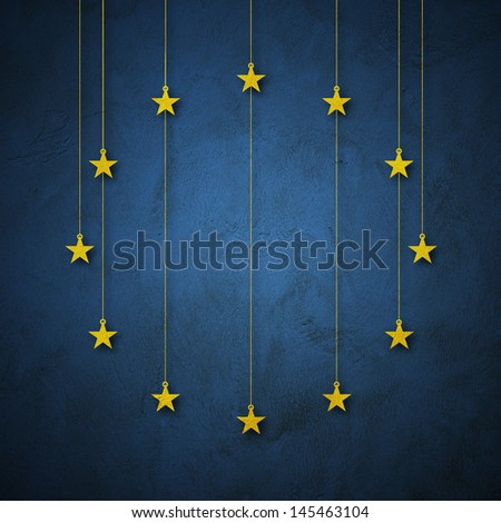 Flag of EU, European Nation. Yellow stars paper cutout hang from roof on blue grunge wall - stock photo