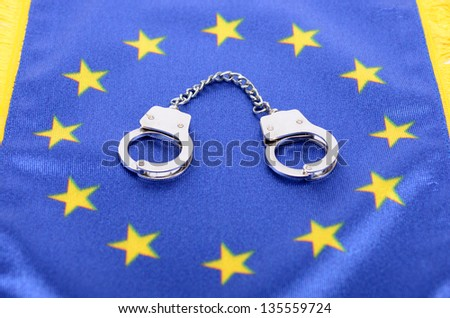 Flag of European Union and handcuffs,  European Union law concept - stock photo