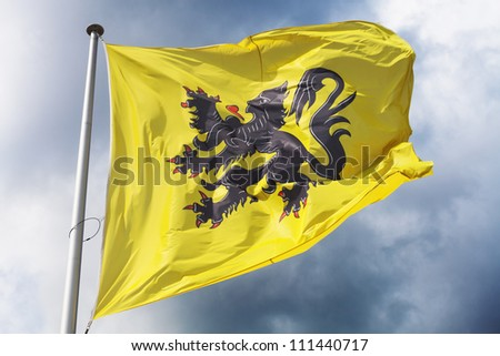 Flag of Flanders (part of Belgium) waving against a dramatic cloudy sky