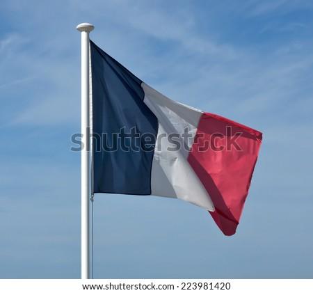 Flag of France waving against blue sky. - stock photo