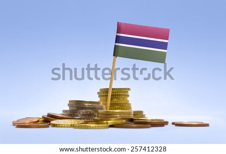 Flag of Gambia in a mixed stack of european coins and a blue background.(series) - stock photo