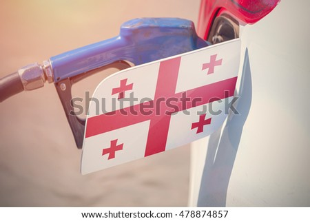 Flag of Georgia on the car's fuel filler flap with gas pump nozzle in the tank