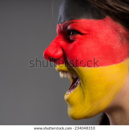 Flag of Germany painted on a face of a young woman. - stock photo