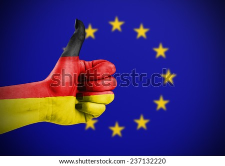 Flag of Germany painted on hand aganinst European Union flag - stock photo