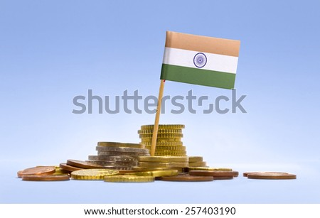Flag of India in a mixed stack of european coins and a blue background.(series) - stock photo