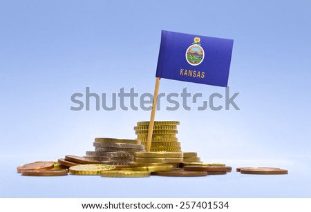 Flag of Kansas in a mixed stack of european coins and a blue background.(series) - stock photo