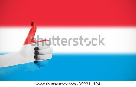 Flag of Luxembourg on female's hand, second, defocused flag in background - stock photo