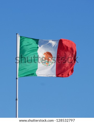 Flag of Mexico flying against blue sky. The Mexican flag is a vertical tricolor of green, white, and red with the national coat of arms charged in the center of the white stripe. Copy space in sky