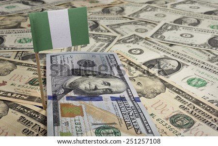 Flag of Nigeria sticking in a variety of american banknotes.(series) - stock photo
