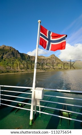 Flag of Norway against the background of a fjord - stock photo