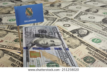 Flag of Oklahoma sticking in a variety of american banknotes.(series) - stock photo
