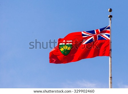 Flag of Ontario flying high on a flag post, against blue sky. The flag is a defaced Red Ensign, with the United Kingdom's Union Flag in the canton and the Ontario shield of arms in the fly. - stock photo