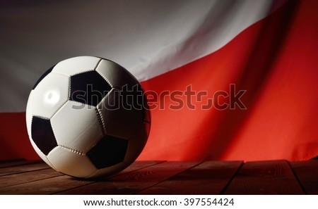 Flag of Poland with football on wooden boards as the background. MANY OTHER PHOTOS FROM THIS SERIES IN MY PORTFOLIO. - stock photo